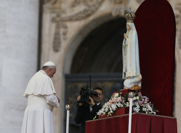 Pope Francis prays in front of the original statue of Our Lady of Fatima during a Marian vigil in St. Peter's Square at the Vatican Oct. 12. The statue was brought from Portugal for a weekend of Marian events culminating in Pope Francis entrusting the world to Mary. (CNS photo/Paul Haring) (Oct. 14, 2013) See POPE-FATIMA Oct. 14, 2013.