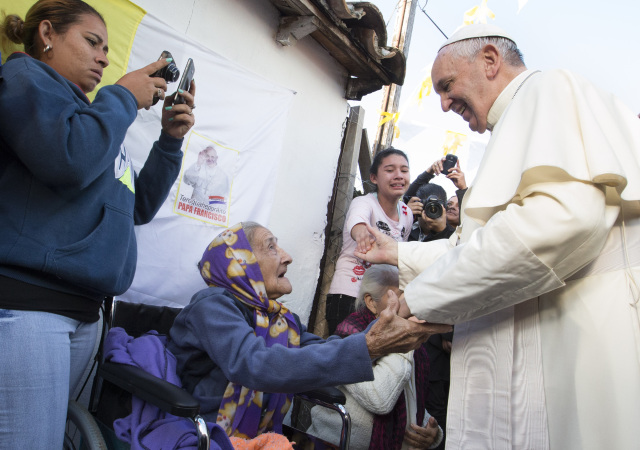 Pope Francis greets an elderly woman as he meets with people of tBanado Norte a poor neighborhood in Asuncion, Paraguay, July 12. (CNS photo/Paul Haring) See POPE-BANADO July 12, 2015.