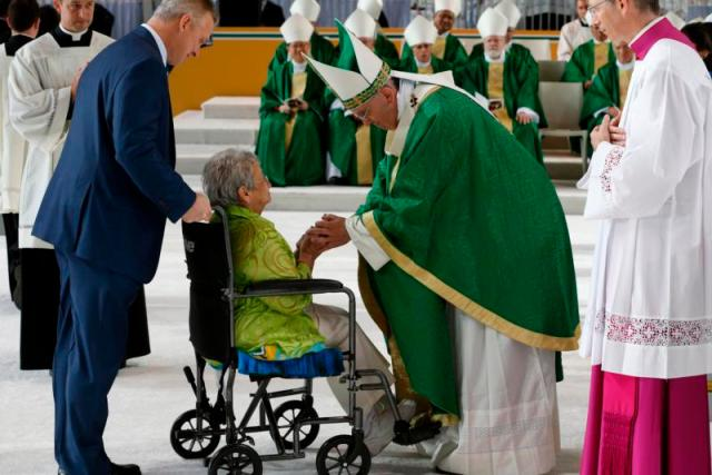 Pope Francis greets a woman in a wheelchair during the presentation of offertory gifts during the closing Mass of the World Meeting of Families along Benjamin Franklin Parkway in Philadelphia Sept. 27. (CNS photo/Paul Haring) See POPE-FAMILY-MASS Sept. 27, 2015.